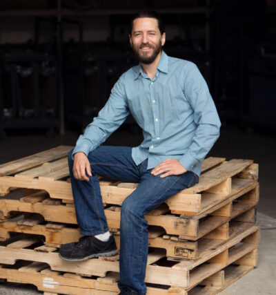 DLO office moving experts - Scott Perry sitting on wooden palette